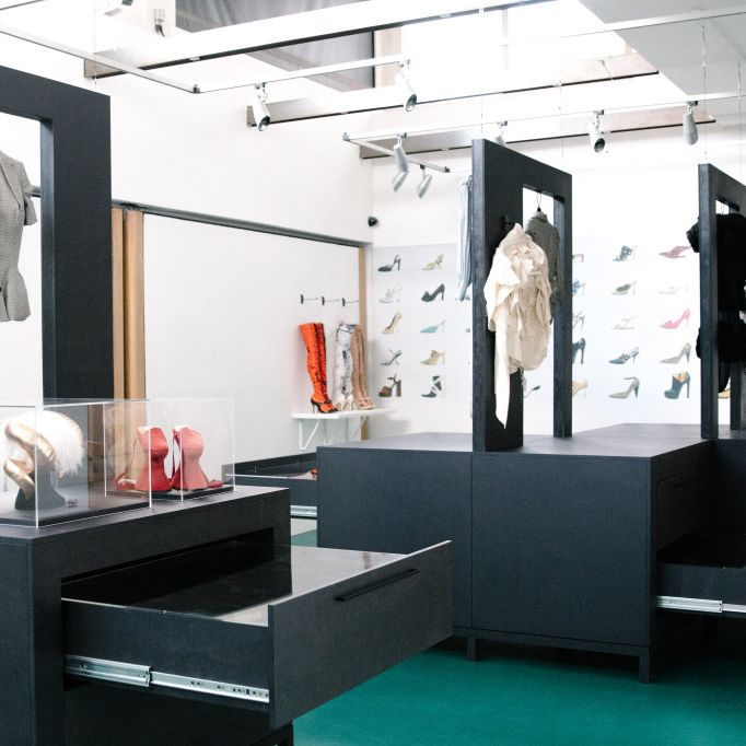 exhibition space with black display cabinets, showcasing hanging womenswear blouses, and perspex boxes with ornaments, in the distance a few stiletto knee high boots. on the far wall a collage print of footwear designs.