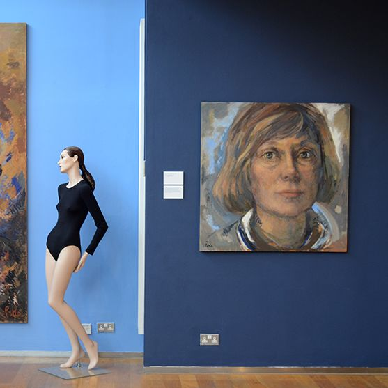 exhibition view of two multicoloured large portrait paintings of Coco Chanel against two blue walls. In between both paintings a mannequin posed wearing a navy unitard.
