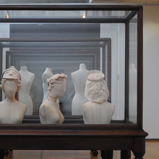 Installation view of three fabric mannequin head and shoulders, wearing different prototype millinery. Left to right, mannequin facing towards camera in a officer style hat, middle mannequin facing right wearing an elegant headdress, right mannequin facing away from camera wearing a hairnet.
