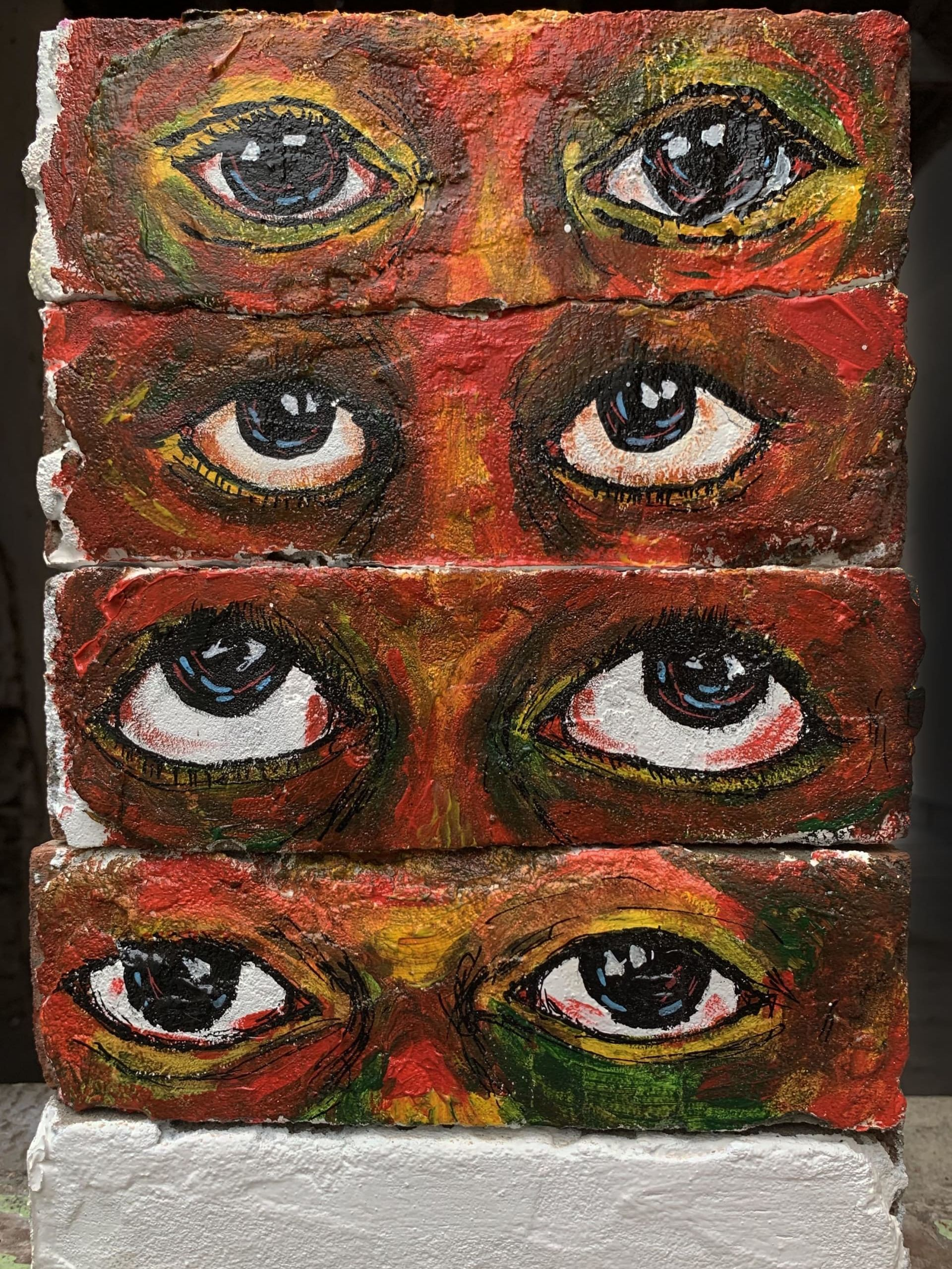 Large scale painting of 4 sets of eyes created using 4 horizontal rows of bricks stacked on top of each other, with intense colours