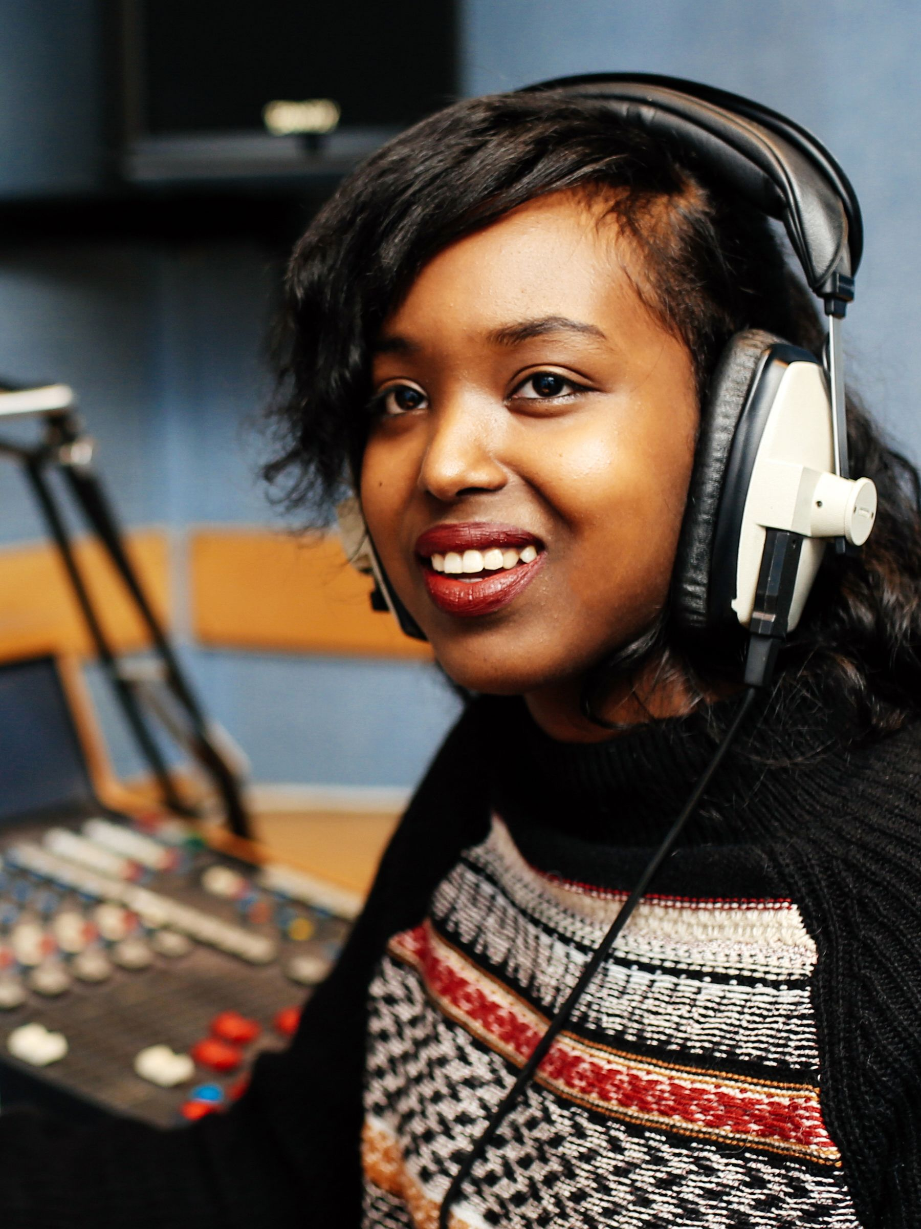 Woman in a radio booth with headphones on and a multicoloured jumper