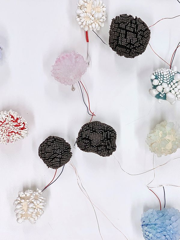 Closeup of pom poms on wires