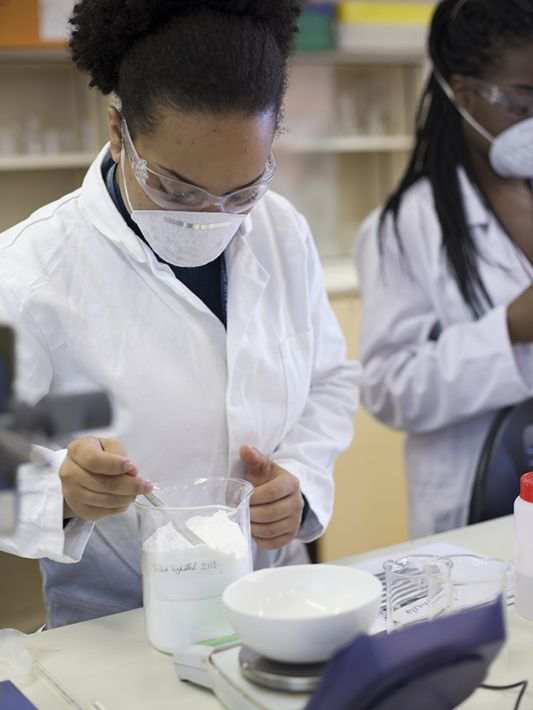 Scientists in labs wearing white robes and using different tools to create cosmetic products