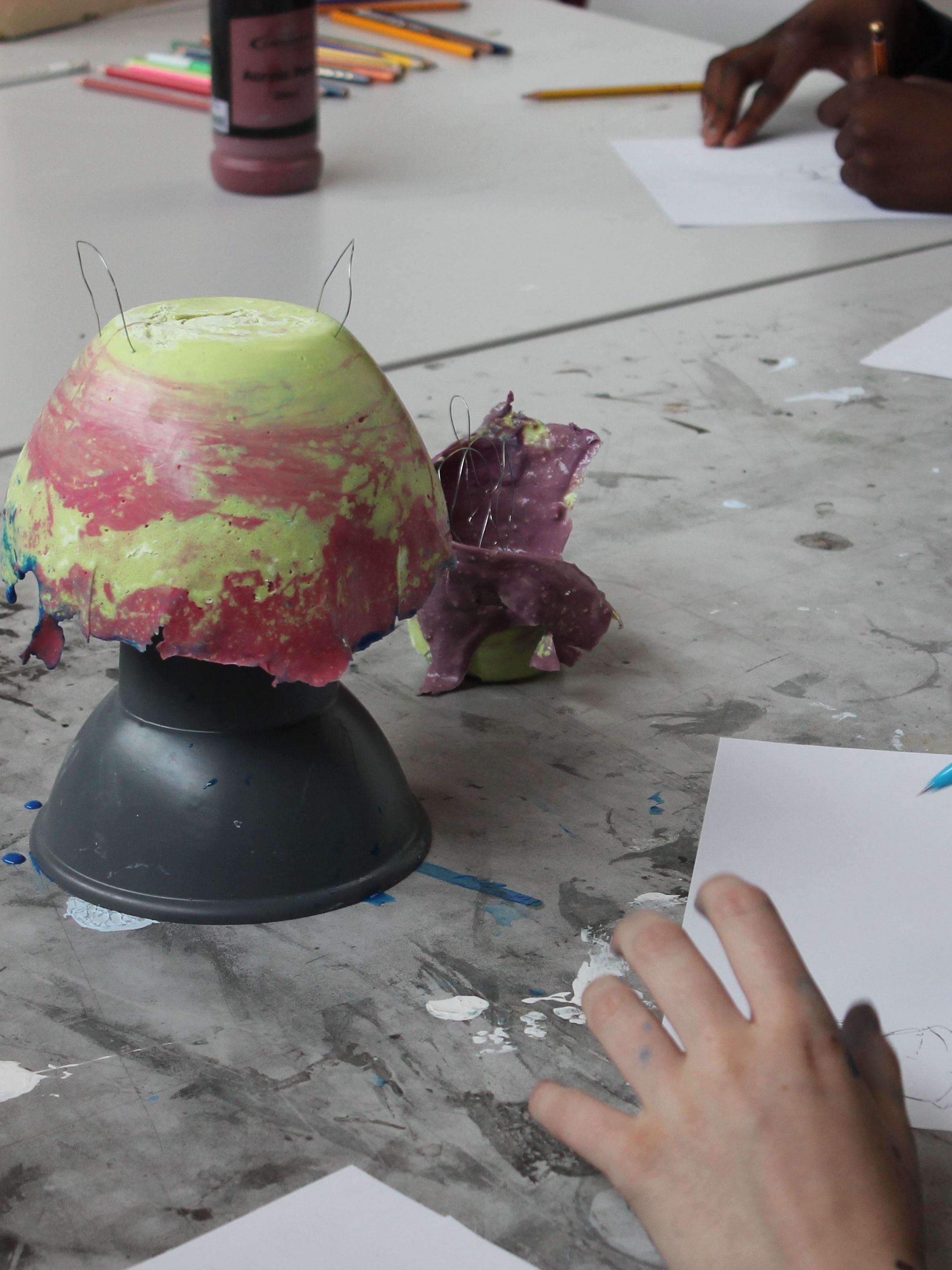 hands gesturing towards a yellow and red sculpture on table. It looks like the sculpture is being observed and drawn.