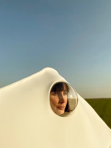Close up portrait of woman wearing voluminous white covering with face looking out of circular window-like feature