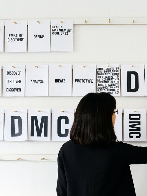 Woman placing cards with letters and numbers on a wall. MA Design Management and Cultures, Ngoc (Sam) Trieu working in the Studio. Copyright holder: Alys Tomlinson