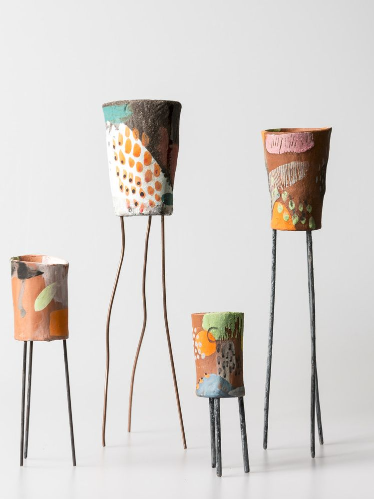 Four colourful ceramic vases each stone on three metal legs