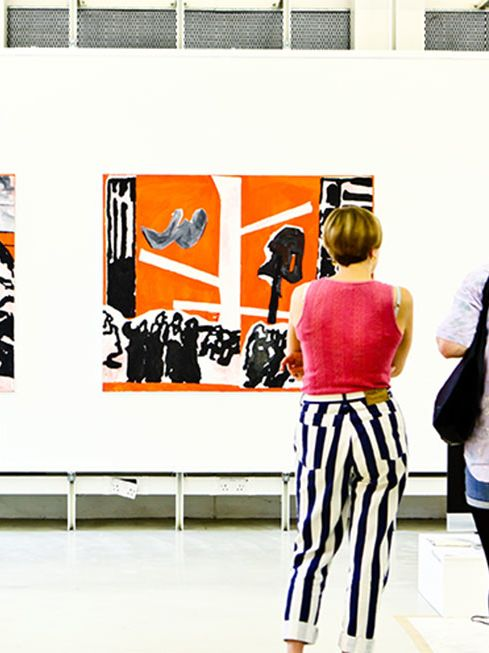 Two people looking at art in a gallery