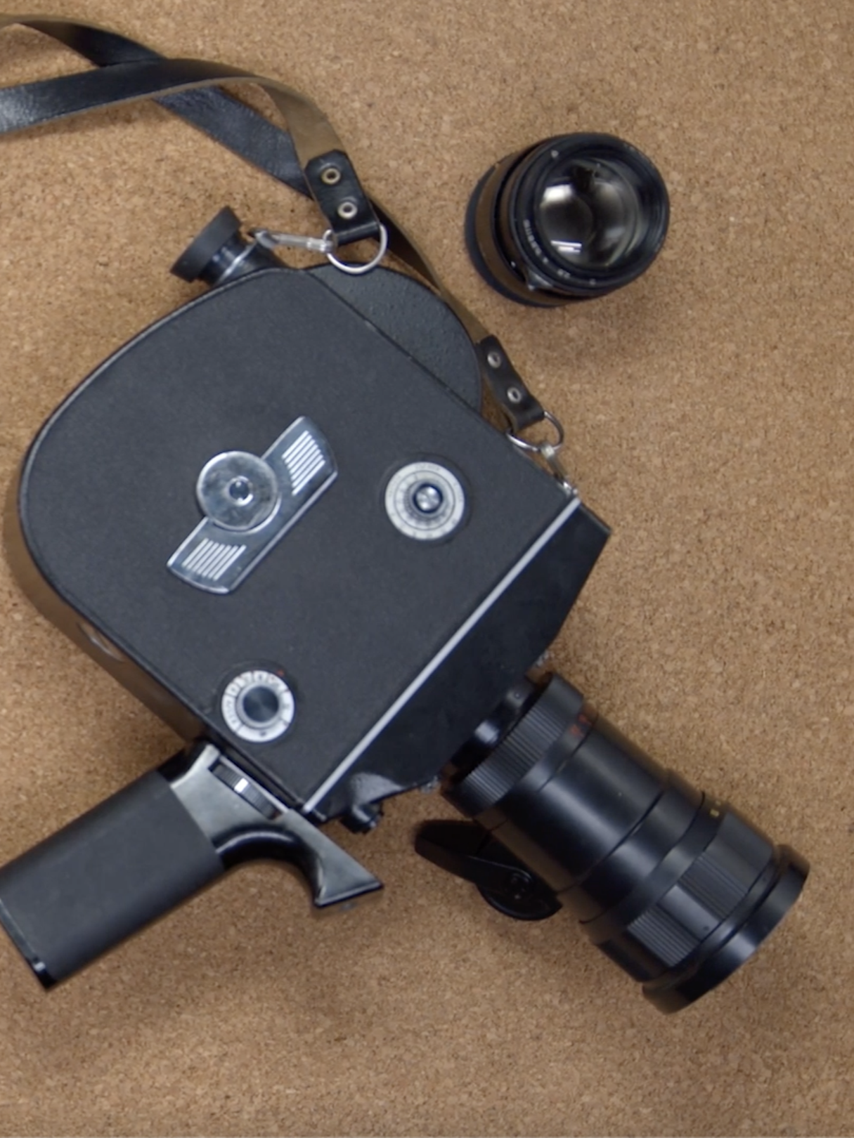 A retor camera lies on a table top with a film clapper board to left out of shot