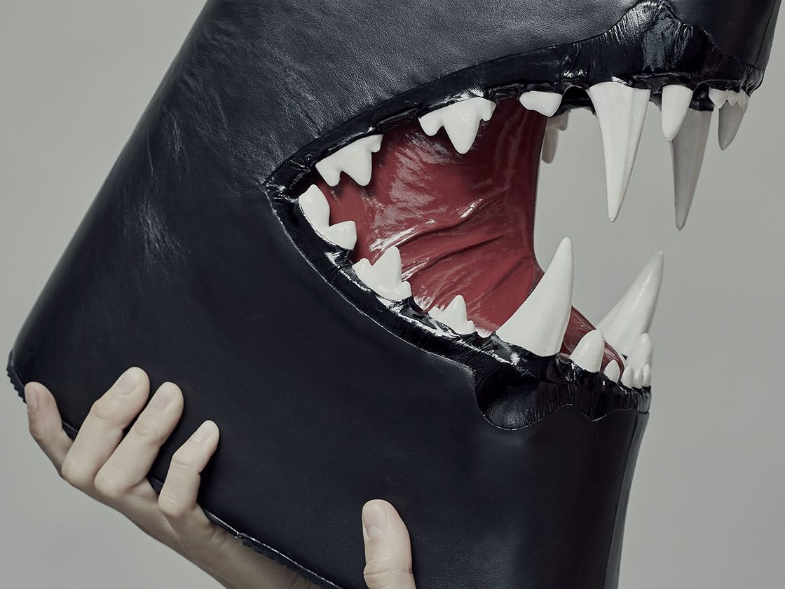 Black boot with sharp teeth held by female model screaming at it