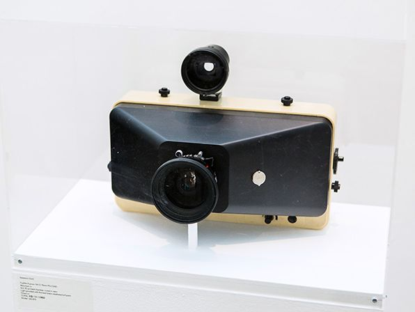 A vintage camera enclosed in a transparent box atop a plinth.