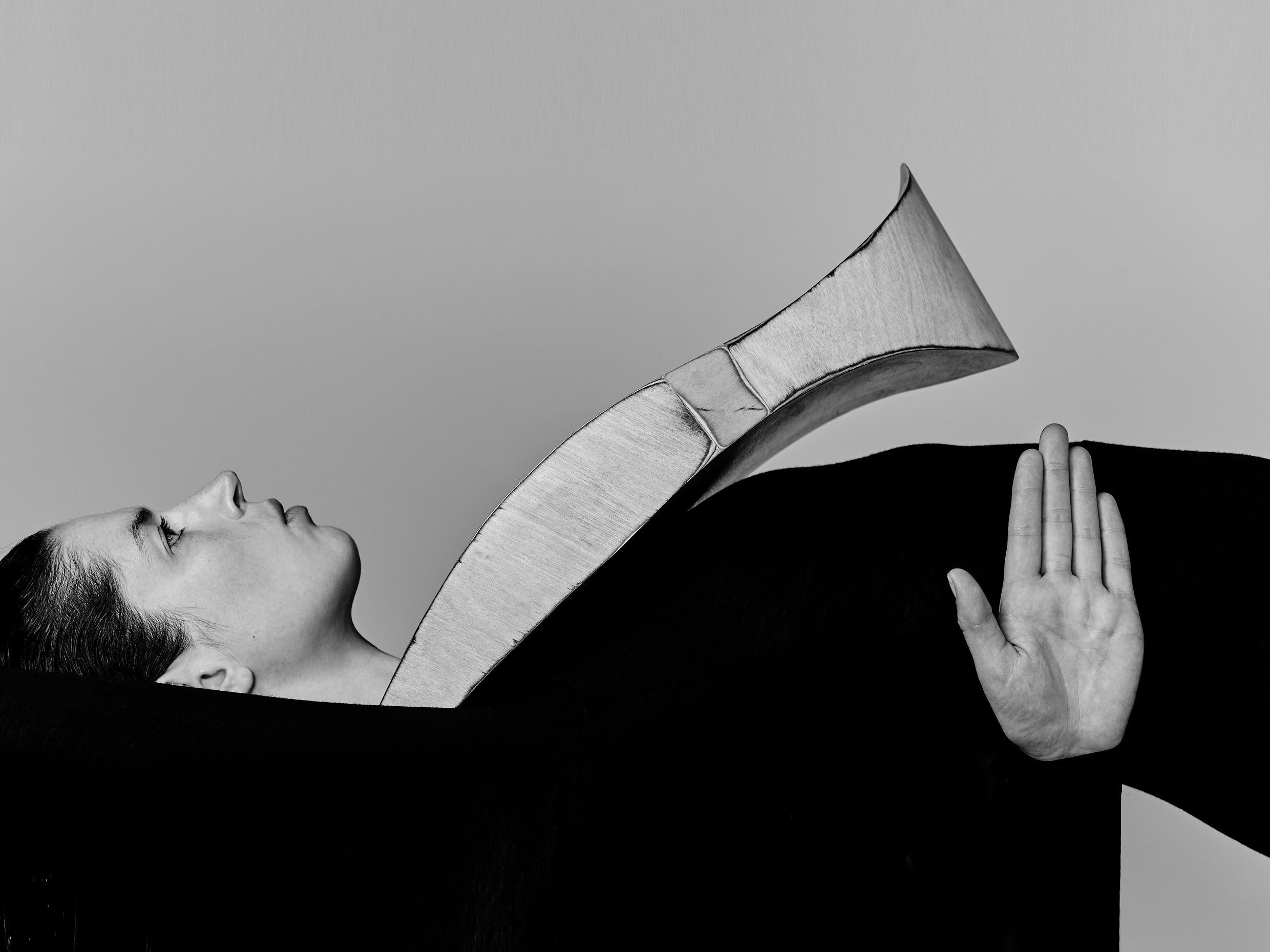 Black and white image of model on their back with extra large accessory on their nexk