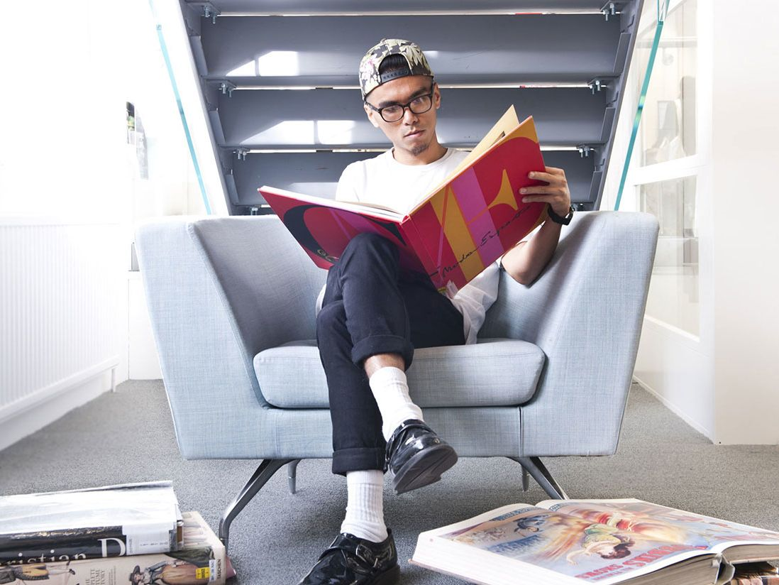 Photo of man sitting in a chair under the stairs reading a large pink, yellow and red book