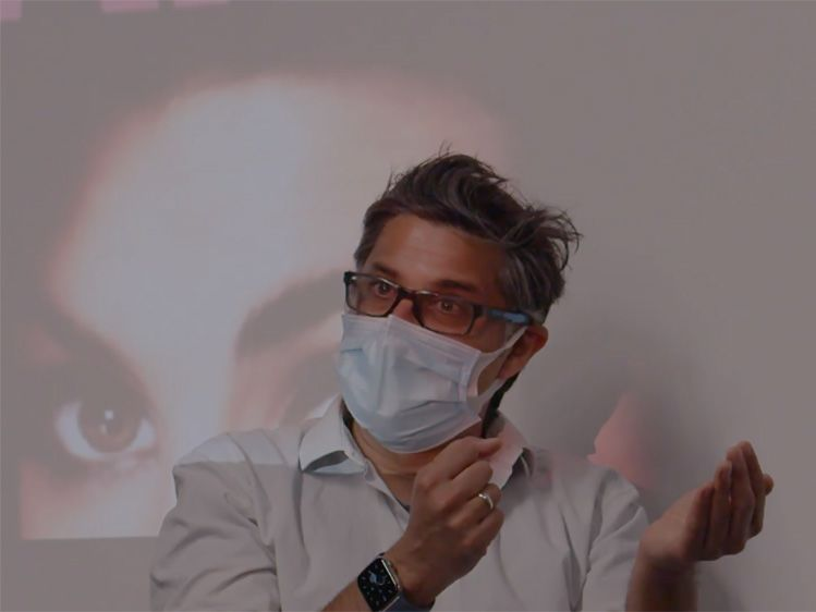 A director wearing a face mask sits in front of a projected screen.