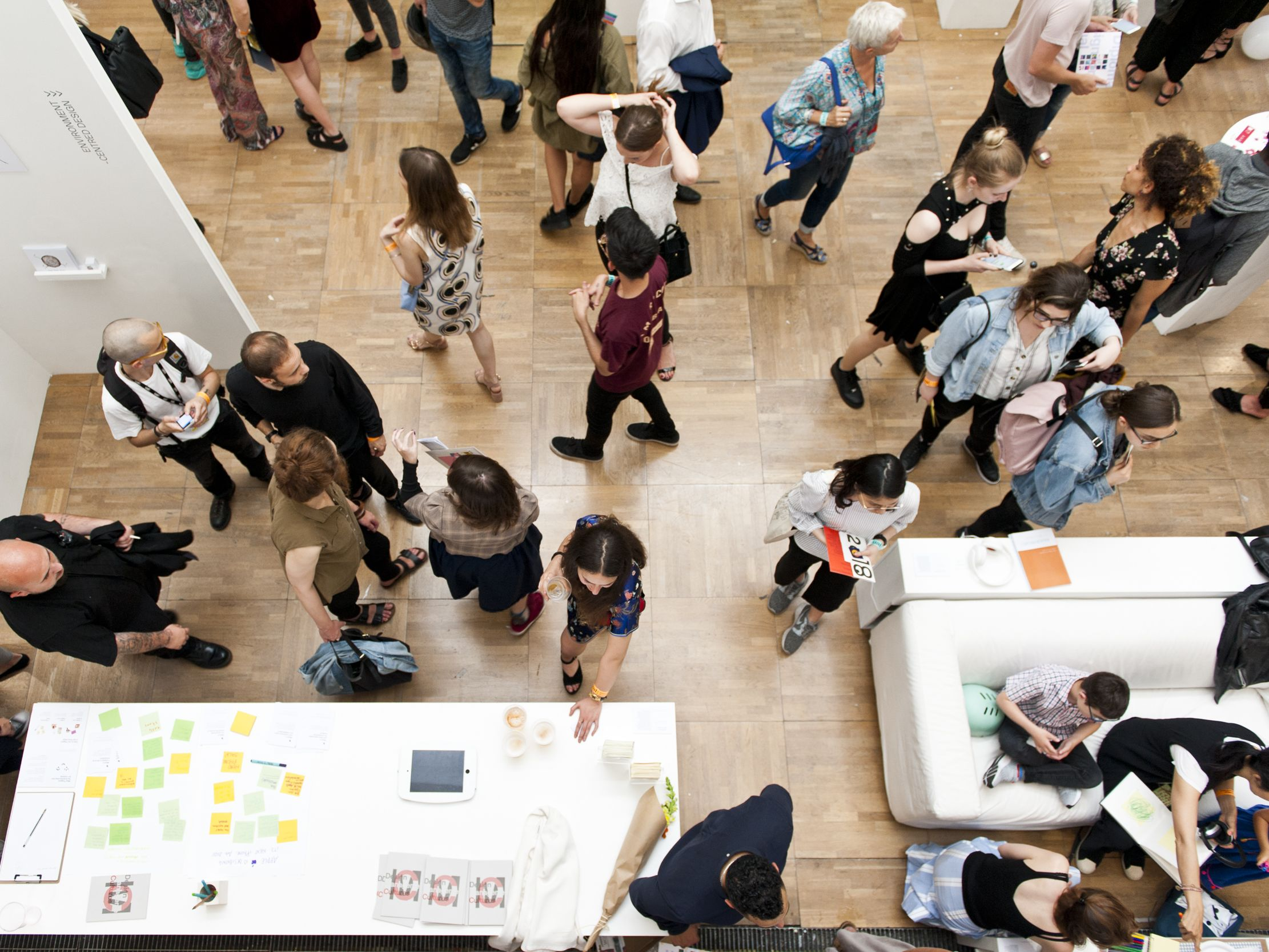 A bird-eye-view of a crowd of people gathered within a gallery space at LCC.