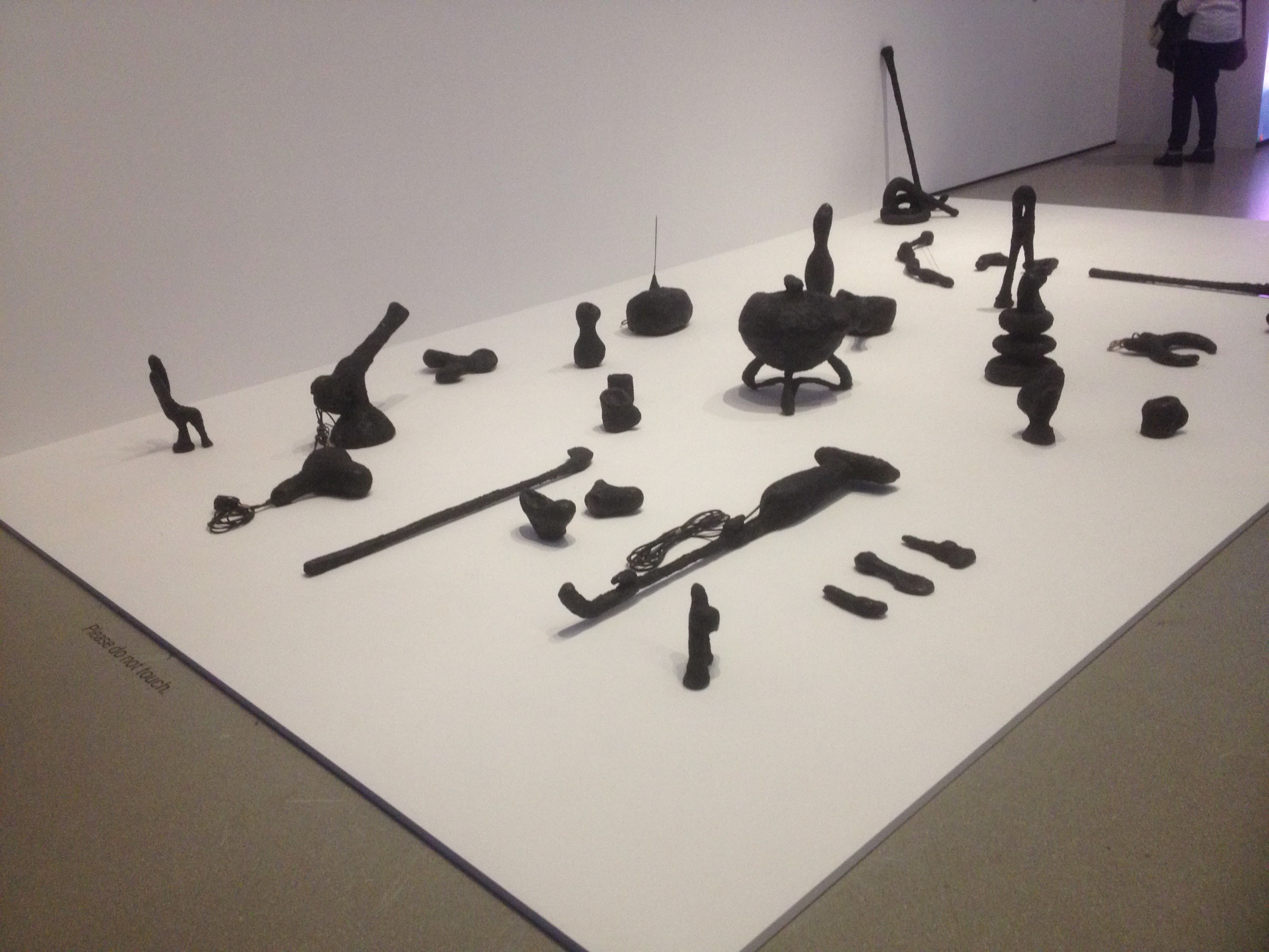 installation shot of camille henrot's sculpture piece augmented objects featuring a  number of objects in black