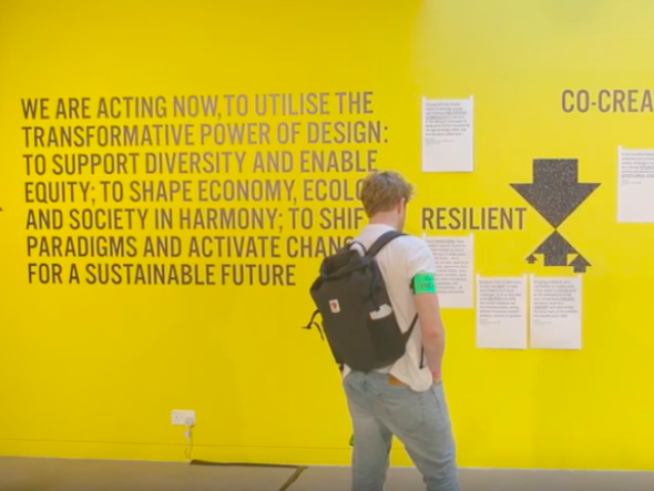 Visitor of London College of Communication's Design School's exhibition and events programme EMERGENCE, viewing a section of the exhibition detailing the principles of the Design School on sustainability.