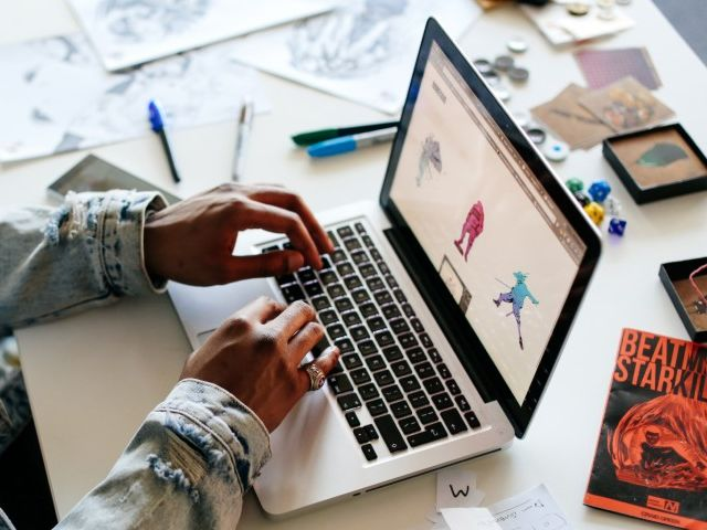 Student in a studio, using a laptop
