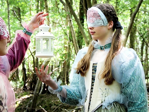 Two masked models interact with eachother while in a forest looking away from the camera wearing garments inspired by the pre-Raphaelite art movement
