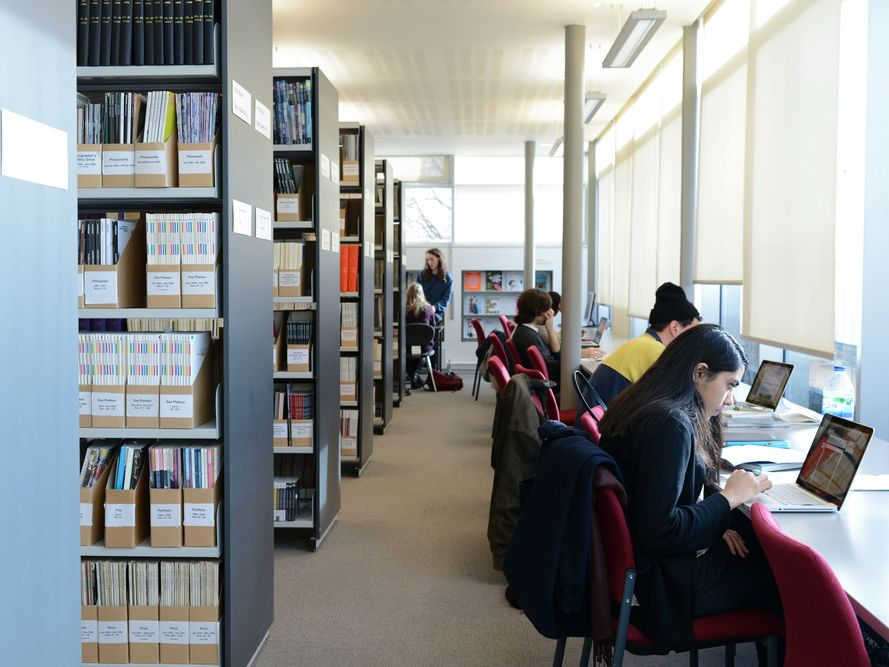 People sitting and working in a library