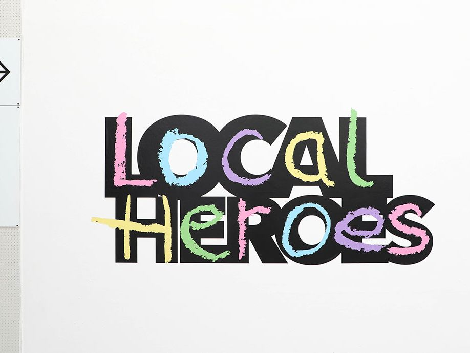 Image depicts a wall exhibit which reads 'Local Heroes' in a large, colourful font.
