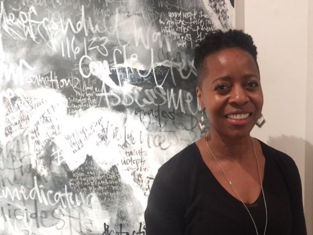 Linett Kamala in front of a black and white painting named 'Courage'