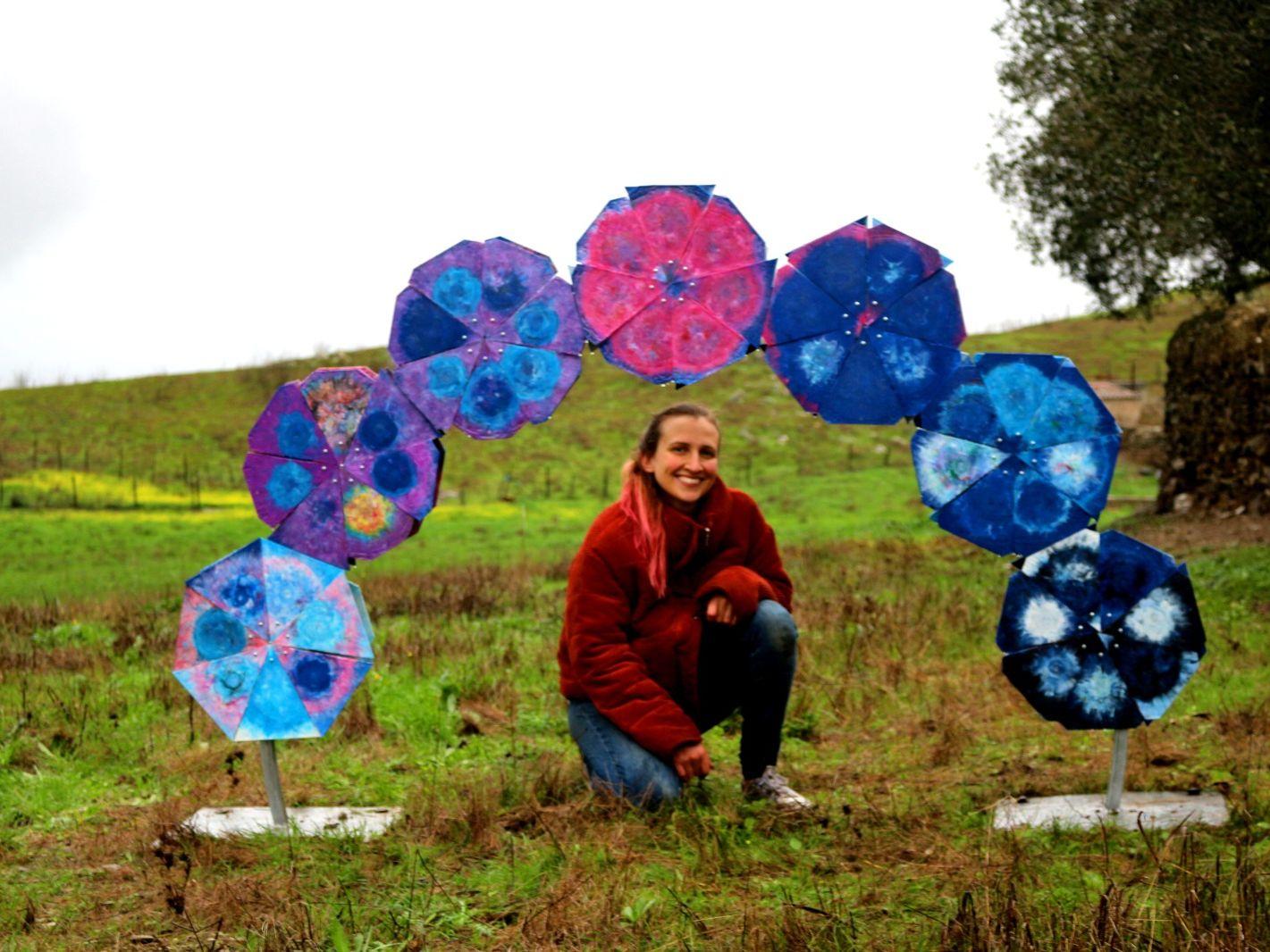 woman squatting in a field under a plastic sculpture