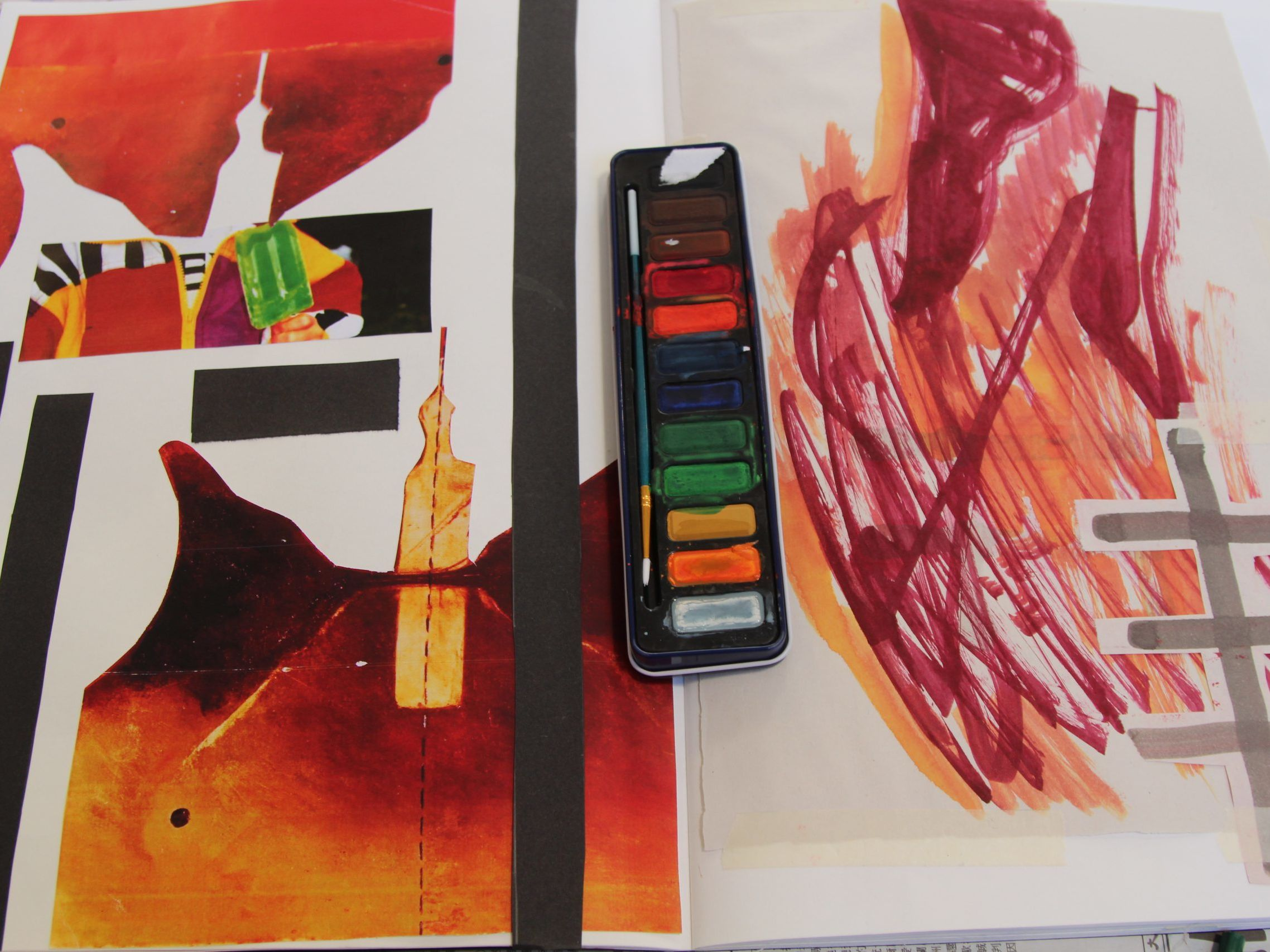 Collage and mark marking in orange and red hues with paint palette central to image