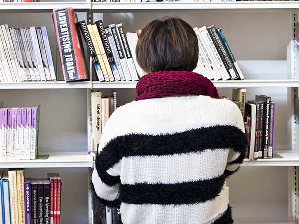 Photo of the back of a person wearing a black and white stripy jumper standing in front of a bookshelf