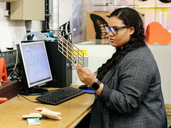Woman looking at 3D printing and sitting at a desk.