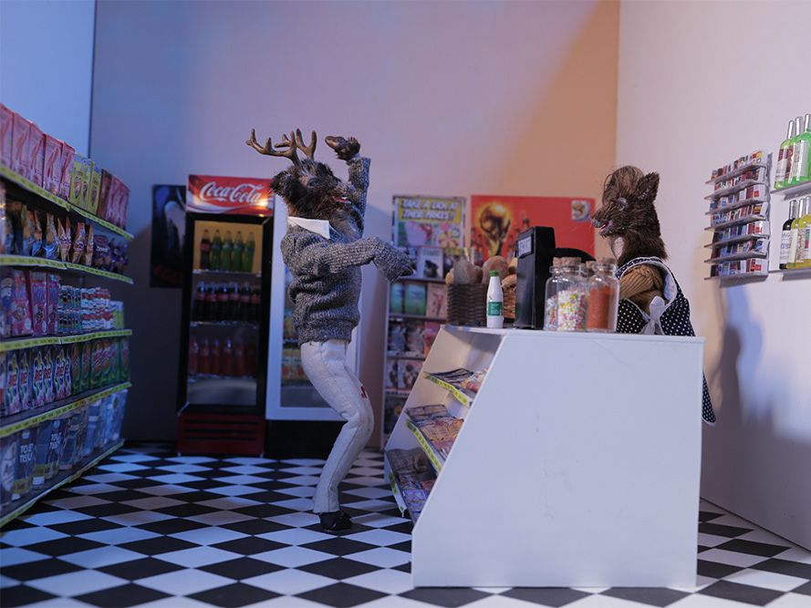 A male model of a deer, taken as a still from a stop motion animated film, waves to another deer in a shop scene.