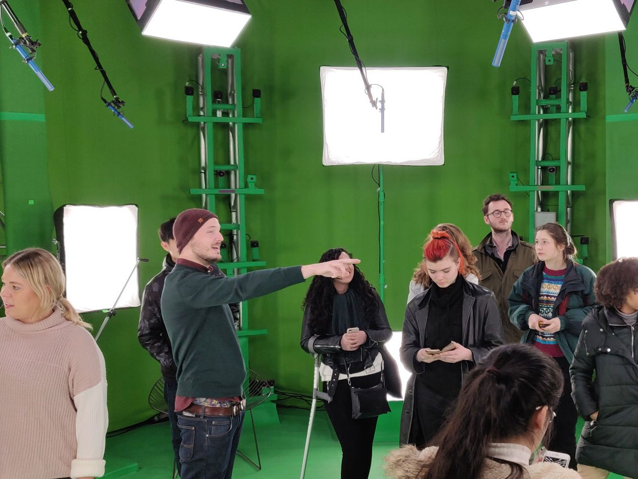A group of people in a green screen room surrounded by large white square lights.