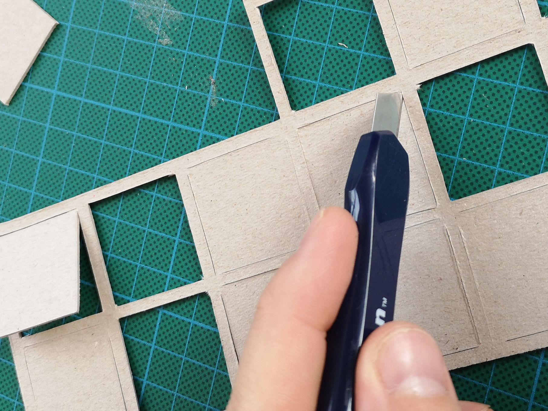 A hand is shown using a craft knife and cutting matt to score out squares from some brown cardboard