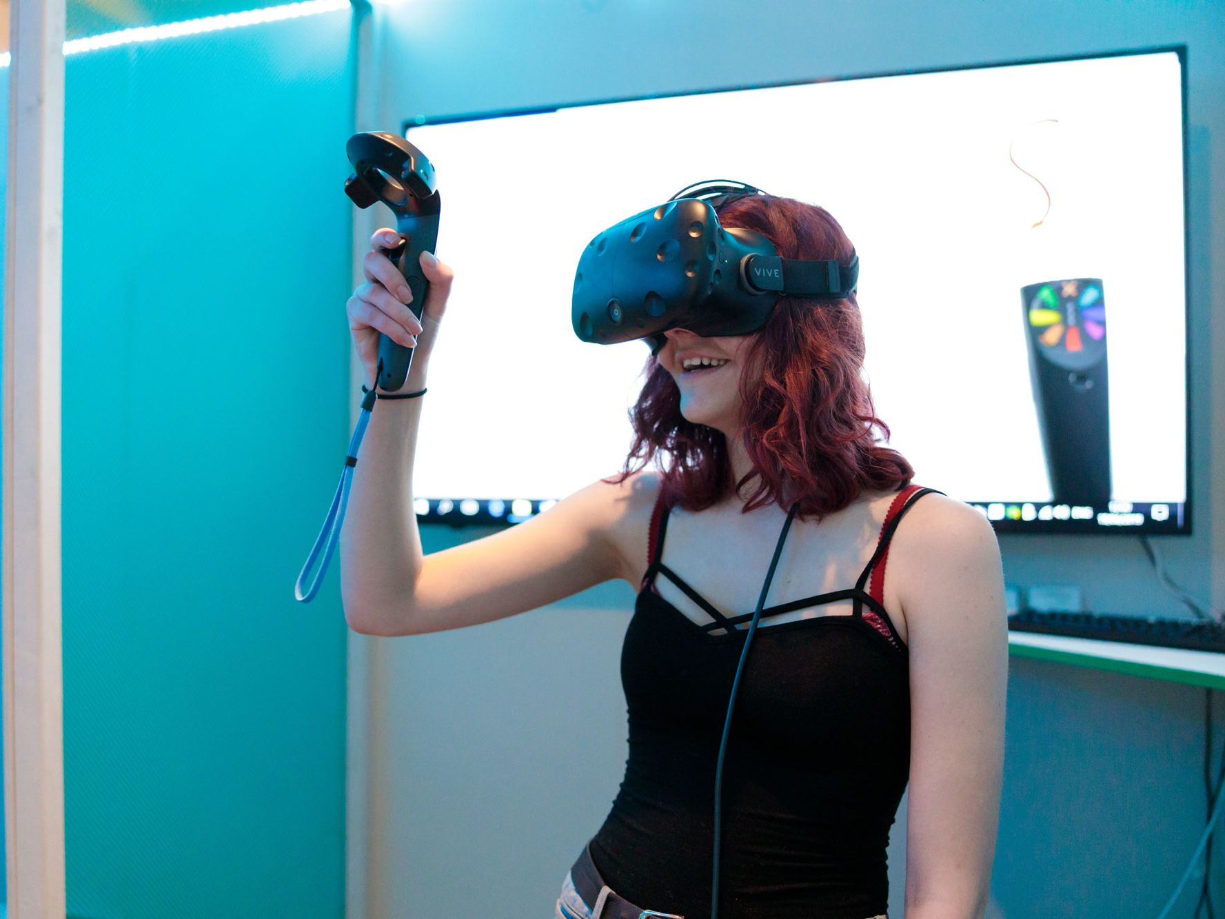 A girl in a black vest stop stands against a blue background wearing a VR headset and holding the controller in her hand, looking upwards.