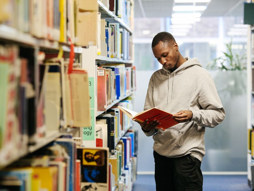Black man reading a publication among library shelves