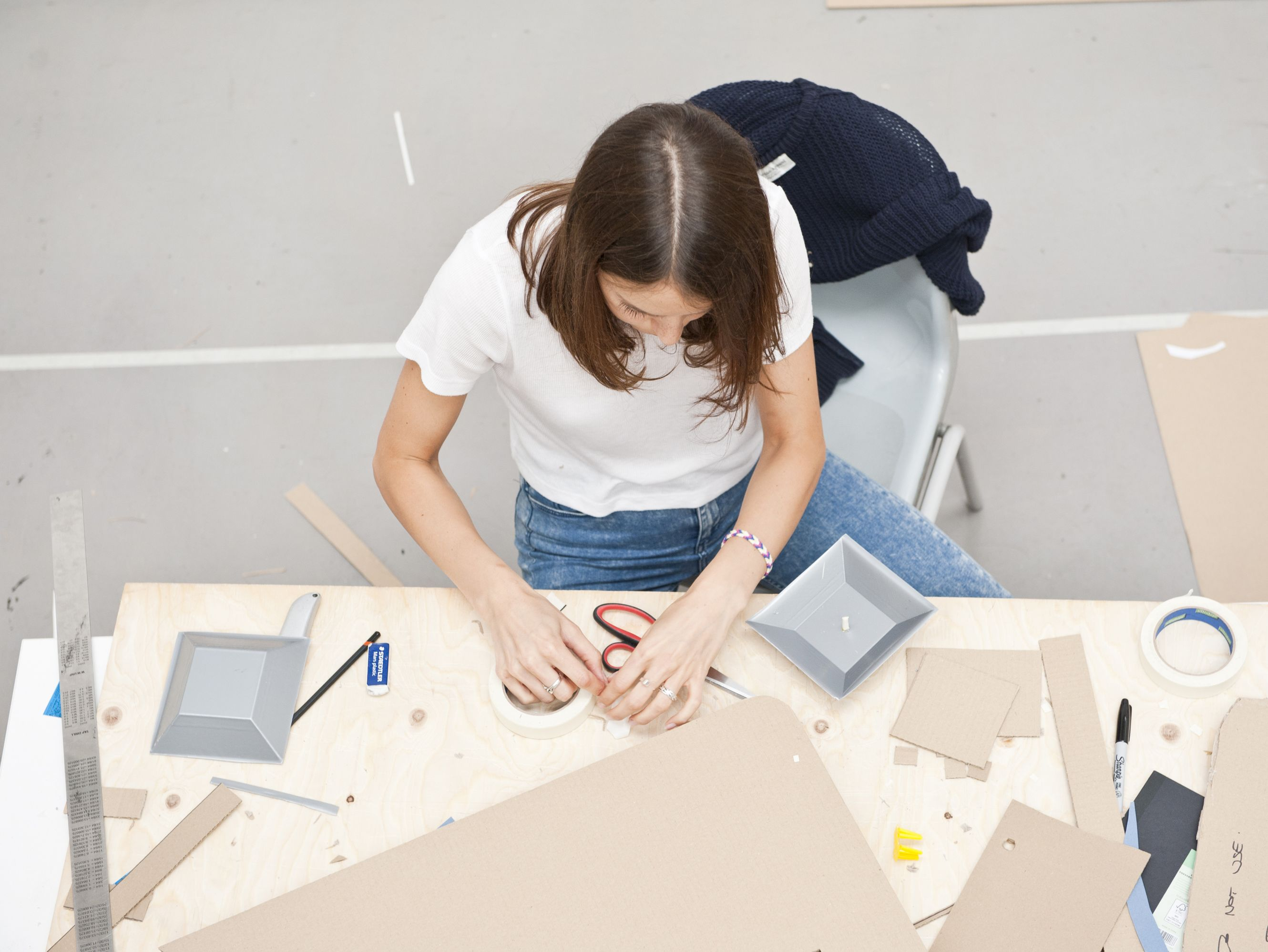 View down to a student seated at a desk and using various tool and cardboard materials.
