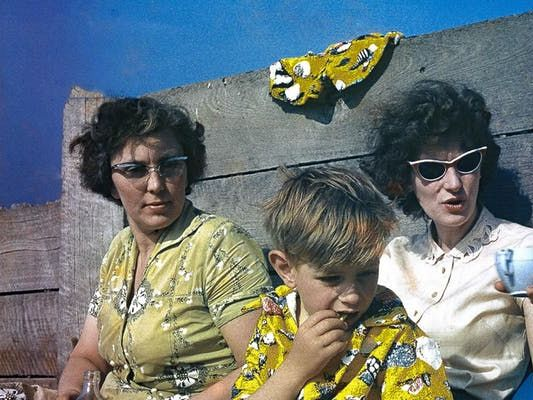 A family, wearing sunglasses, sit on a beach and drink tea.