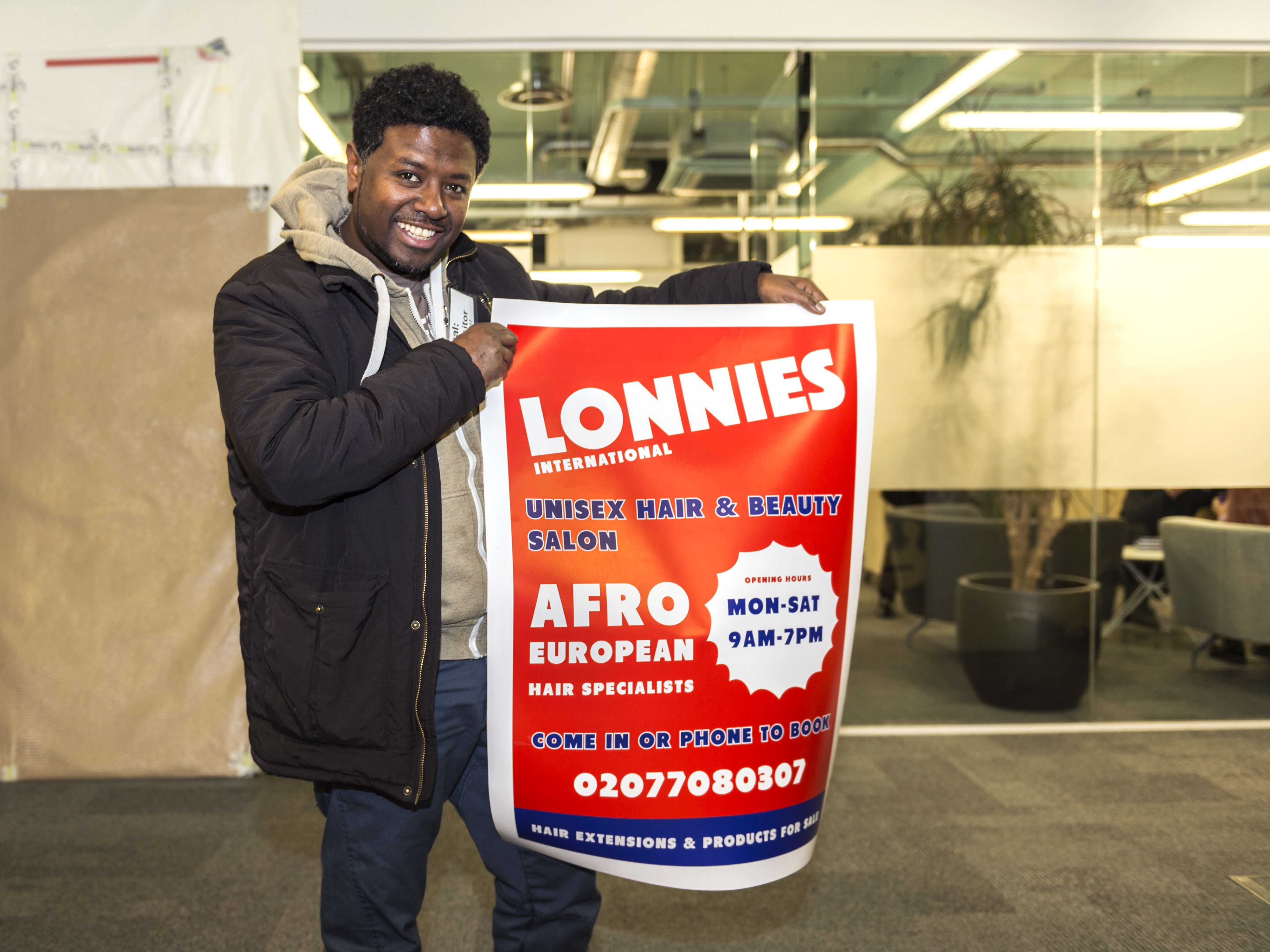 Photograph of a man holding a shop poster.
