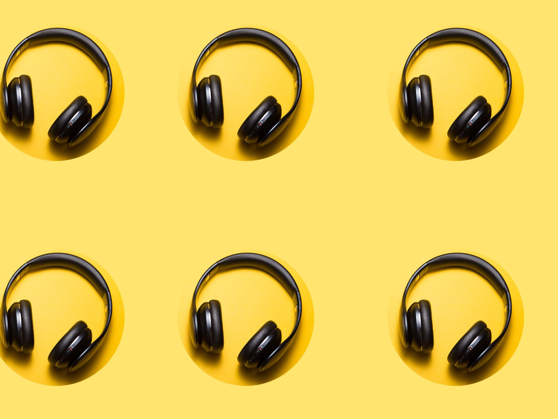 Repeat pattern of 6 black on ear headphones on yellow background