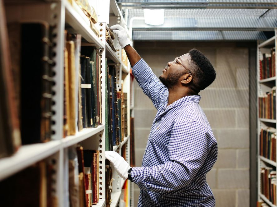 Black man researching in archives wearing white gloves
