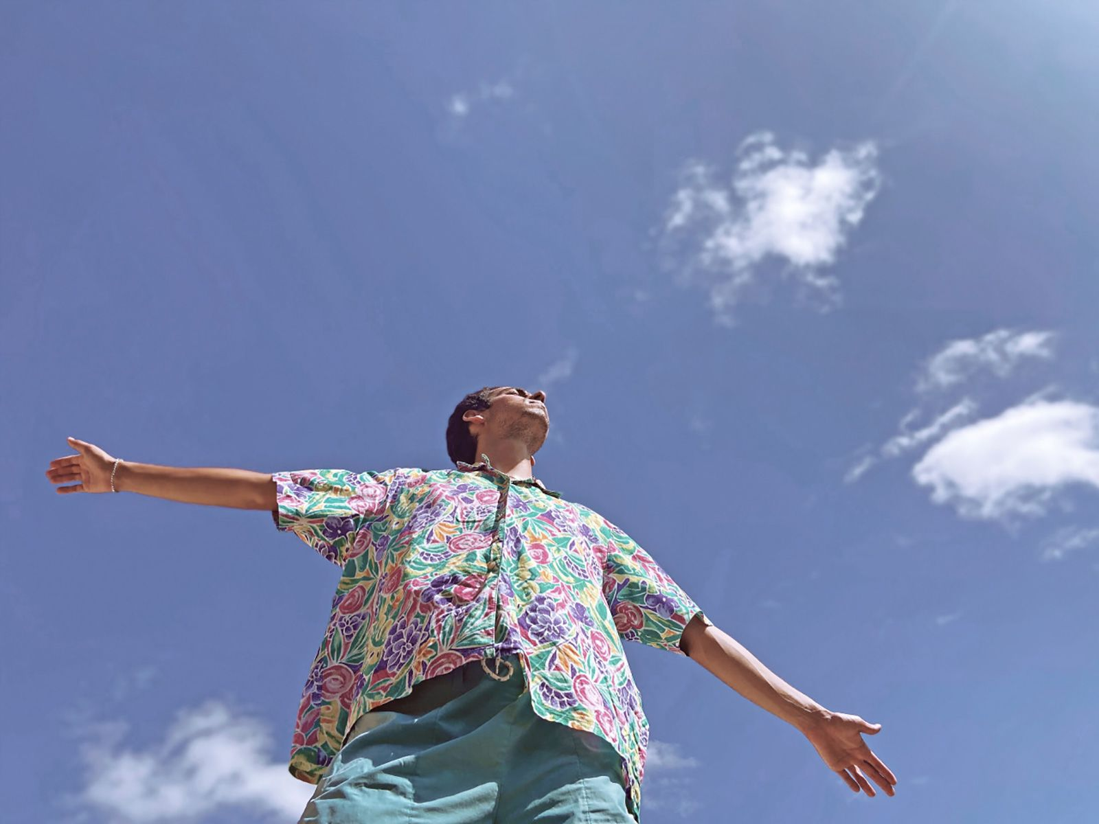 A photograph of a man raising his arms to a blue sky.