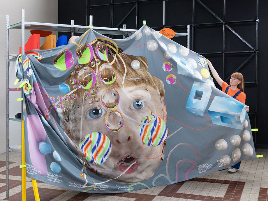 An artist stands beside a bedsheet-sized artwork depicting a face surrounded by coloured bubbles.
