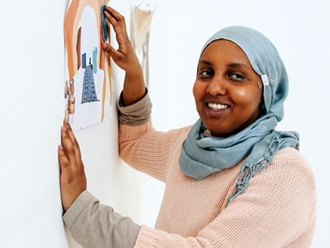 Student with art work on wall