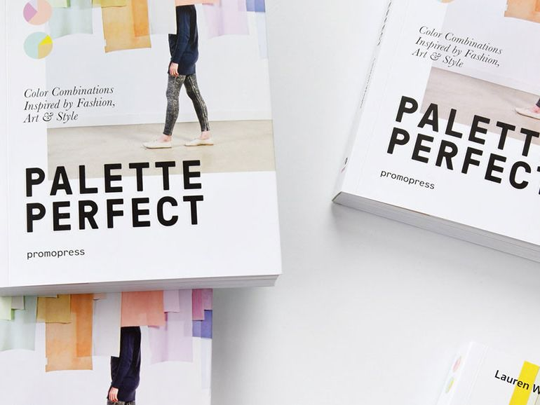 An arrangement of copies of Palette Perfect, the covers of which feature a single figure walking across a gallery space filled with hanging colour banners.