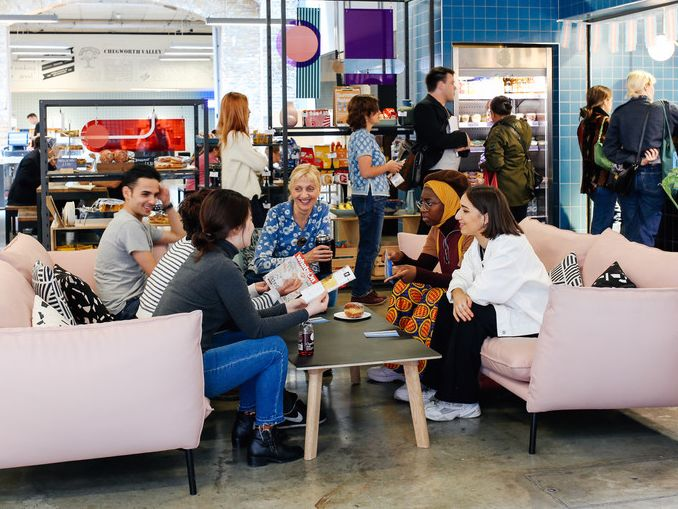 A group of 5 students and 1 tutor sat on 2 large pink sofas in a cafe, discussing projects and smiling.