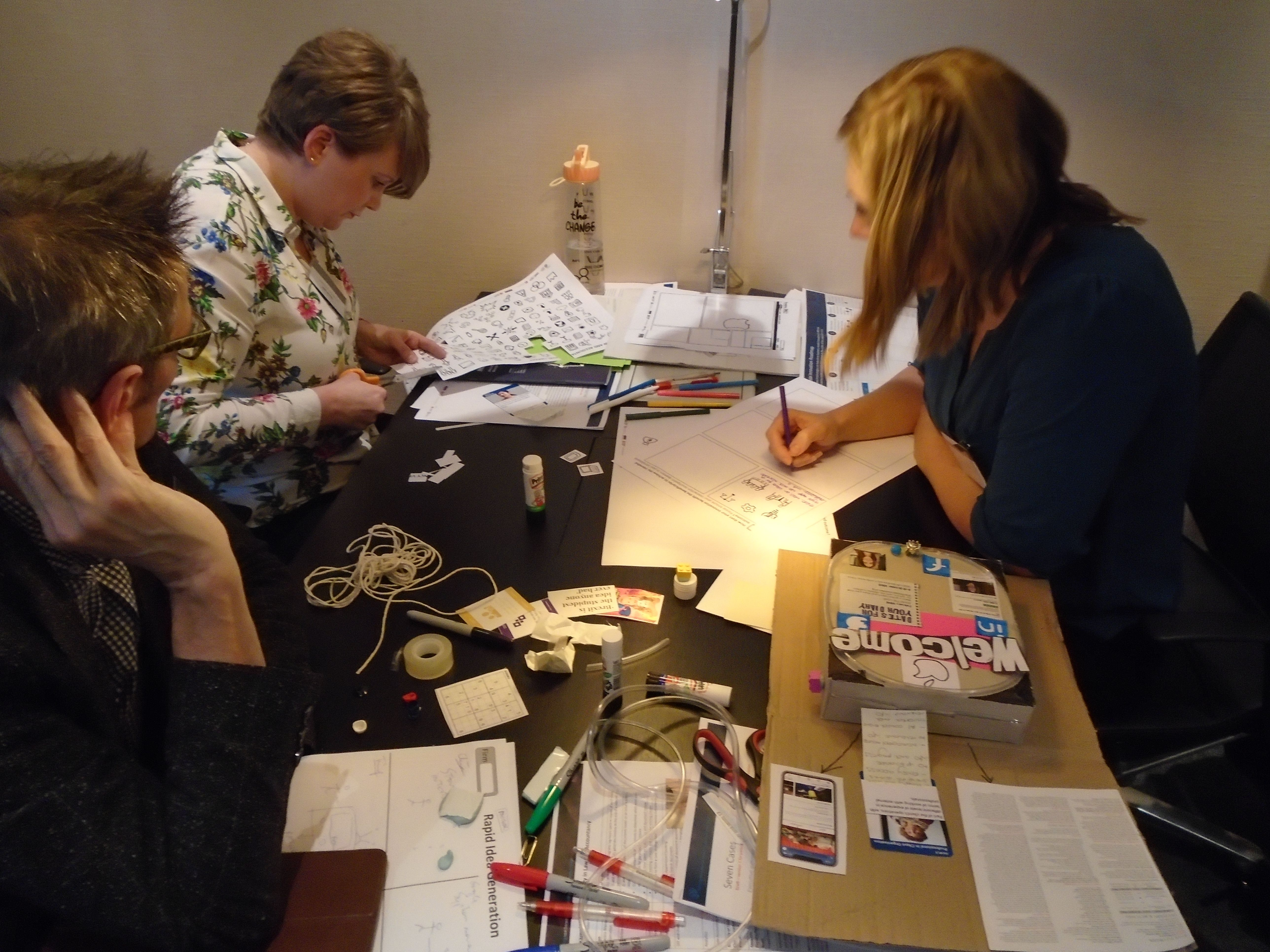 People working at a table with lots of papers and materials on the desk