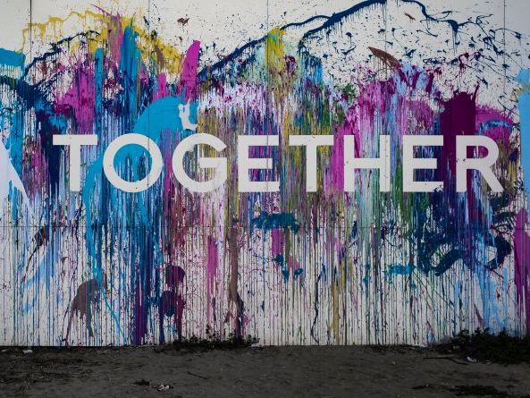 White wall covered in purple and blue paint with stencilled word 'together' visible