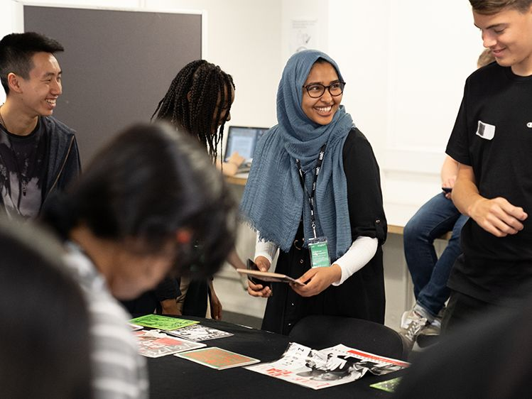 A group of students stand together looking at zines, talking and laughing