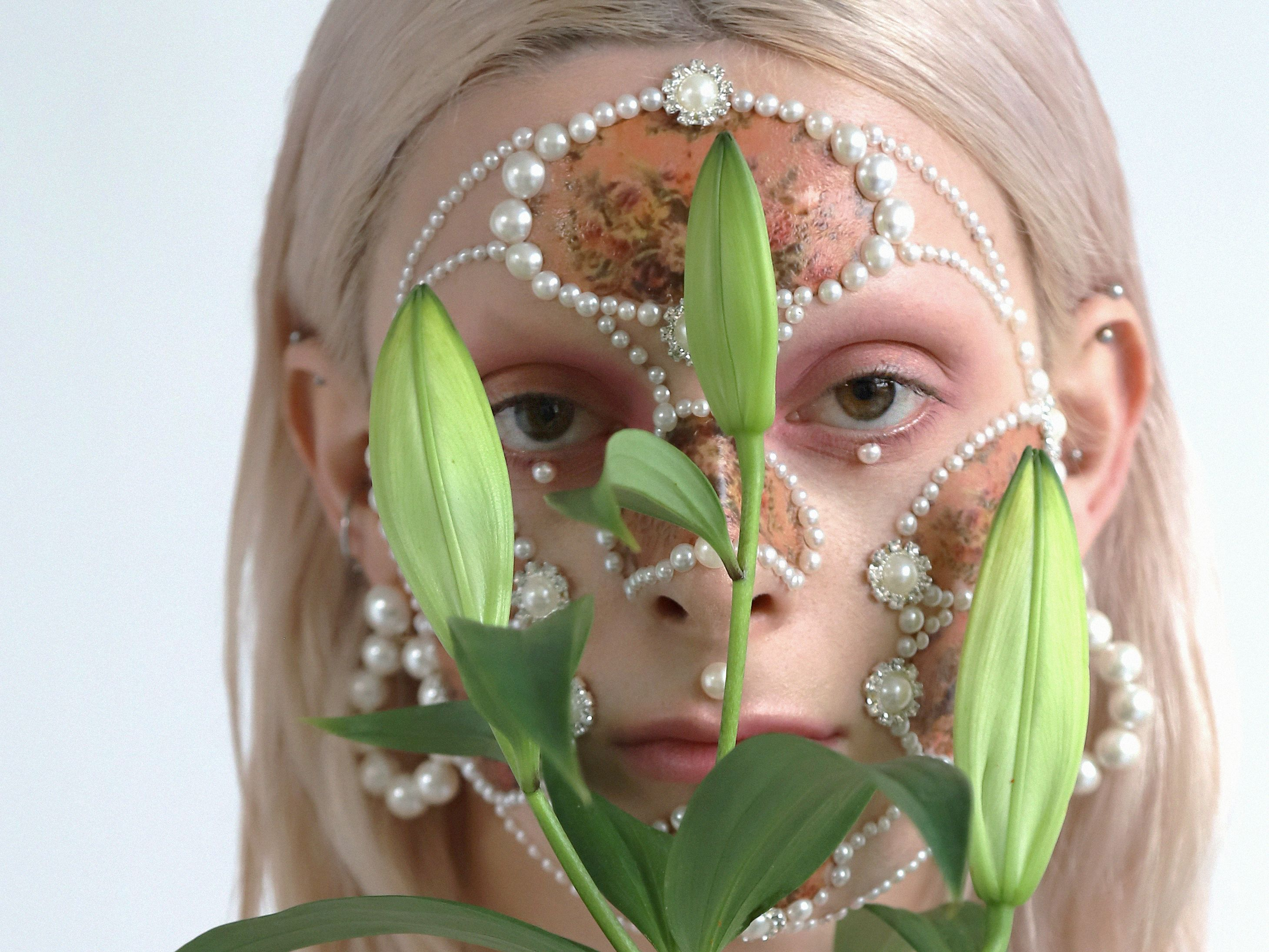 Female model with pearl facial jewellery, makeup and lillies.
