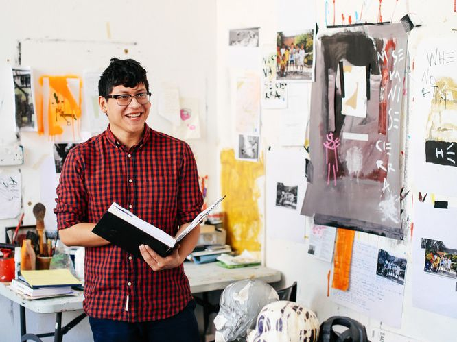 Boy in studio surrounded by sketches
